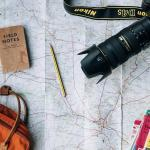 Camera and bag and notebook lying on a map