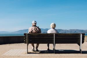 two people sitting on bench watching view