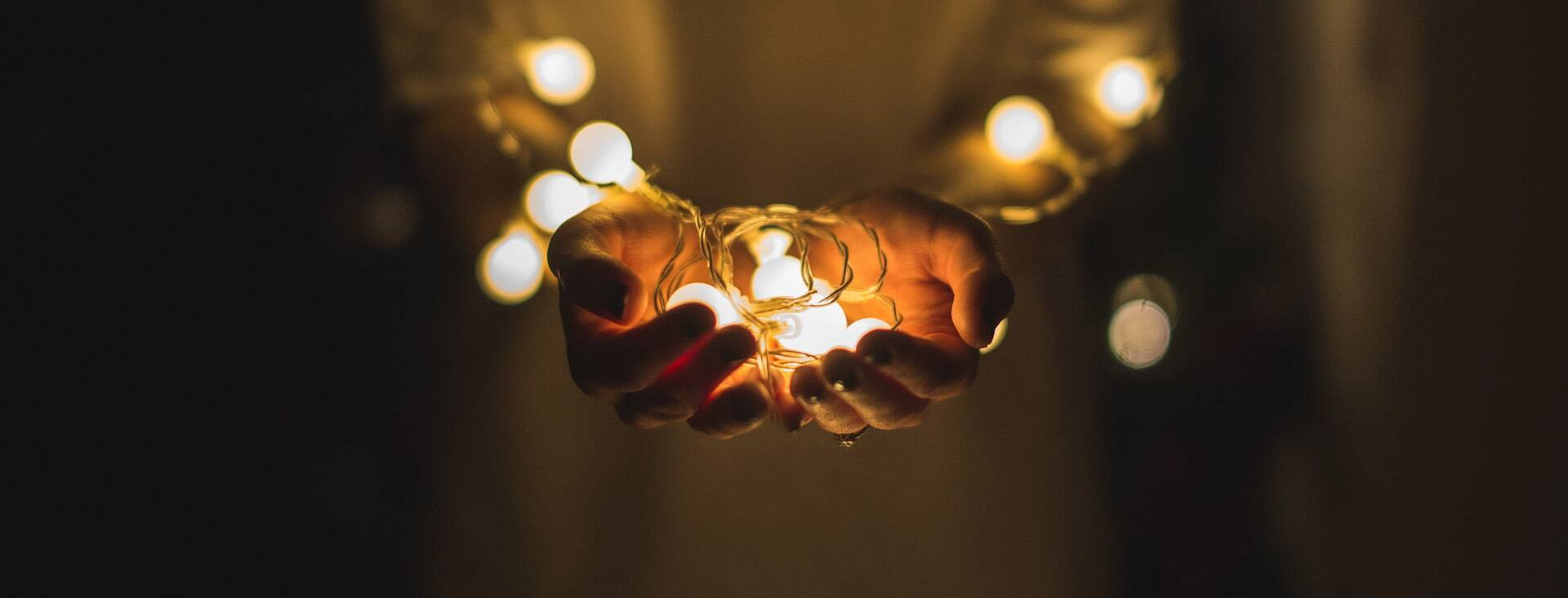 Two hands holding fairy lights