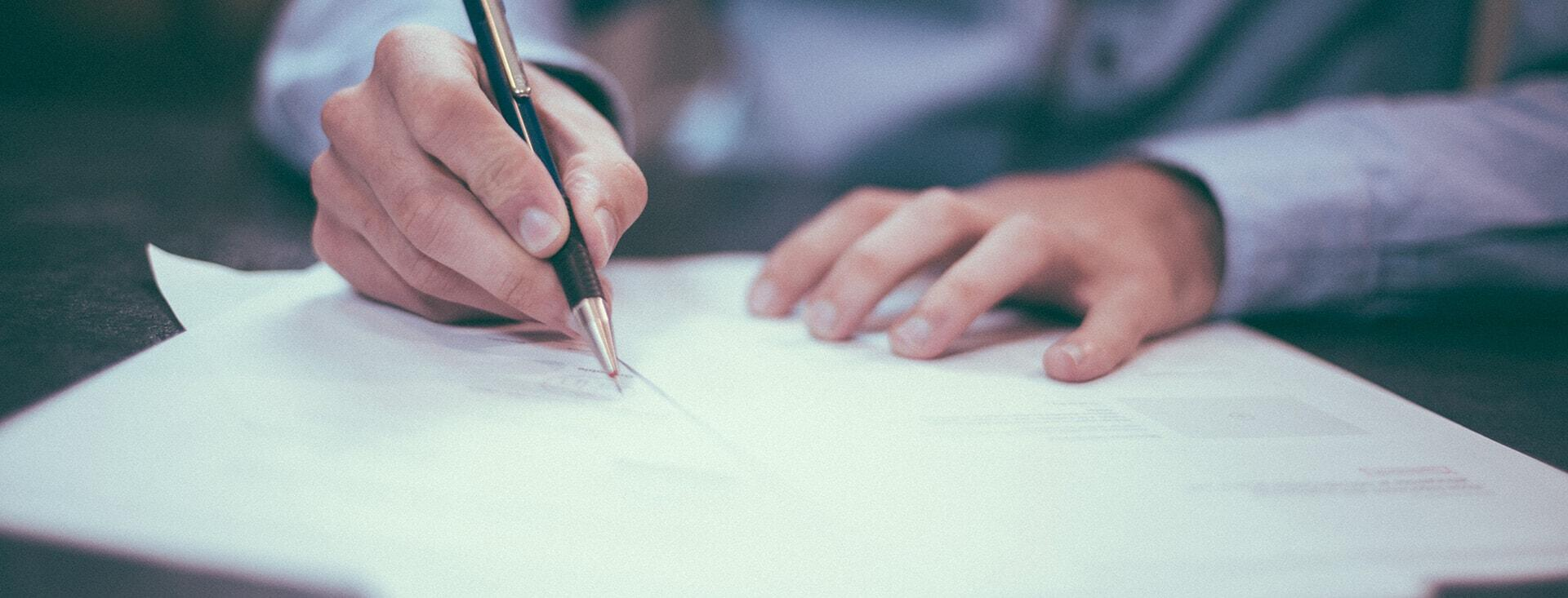 Man writing on paper on a desk