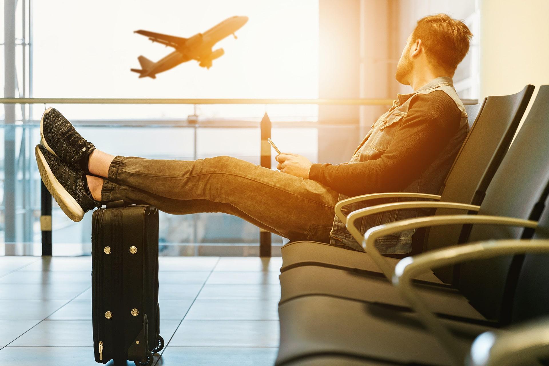 Man waiting at airport watching plane take off